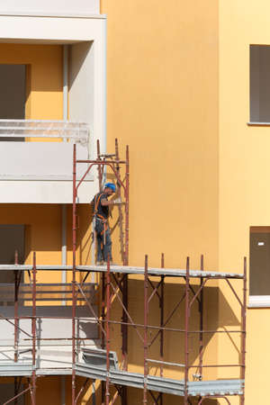 Worker with Blue Hardhat at Work on a Scaffold in a Building Site for the Construction of a Building.
