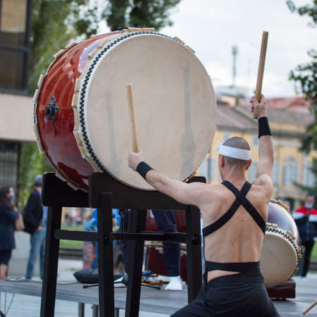 Man with Headband Playing Vertical Drum of Japanese Musical Tradition during a Public Outdoor Event.