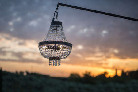 Precious Glass Chandelier exposed Outside at Sunset. Imagens