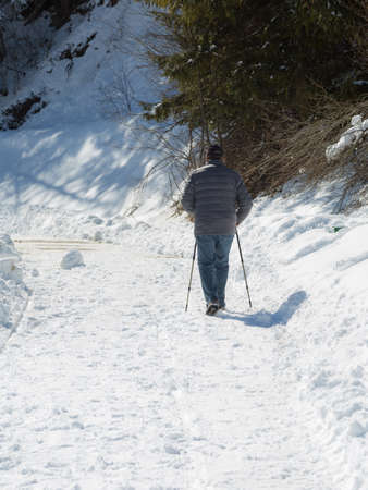 Rear View of an Old Man Walking on a Snowy Road with the Support of Sticks. Imagens