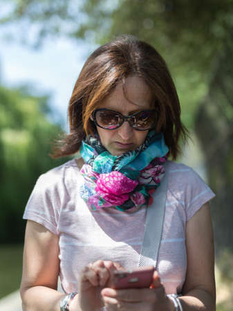 Portrait of a Middle-aged Woman with Glasses and Scarf using her Mobile Phone.