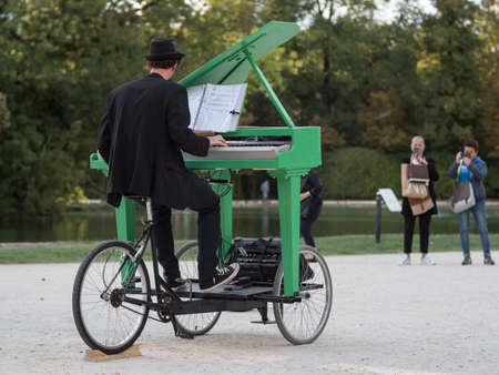 Pianist with a Hat Playing a Green Mobile Piano in a Public Park.