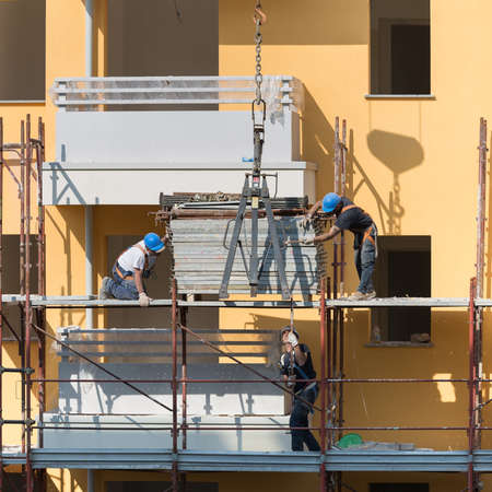 Workers at Work on a Scaffold in a Building Site for the Construction of a Building.