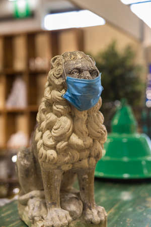 Marble Statue of a Lion Wearing a Surgical Mask.
