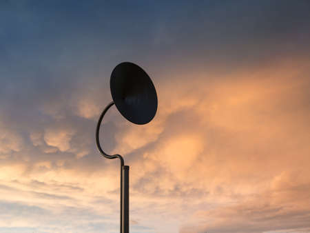 Circular Satellite Dish and Cloudy Sky at Sunset.