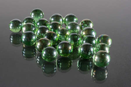 Small Emerald Green Glass Balls with Reflection and Black Background. Фото со стока