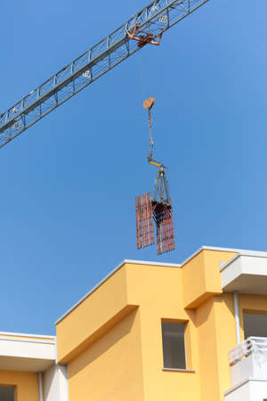 Detail of a Crane Lifting some Pieces of Scaffolding over a New Building.