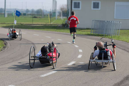 Disabled Athletes training with their Handbike with Runner Close to Them.