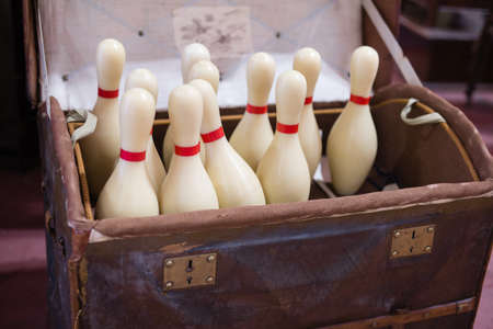 Set of White Bowling Pins inside an open Casket.