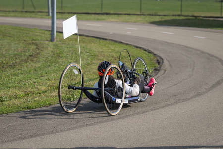Athlete Girl with Helmet Riding her Hand Bike on a Track. Standard-Bild