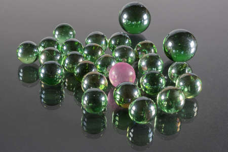 Small Emerald Green Glass Balls with Reflection and One Pink Ball.