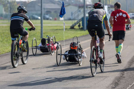 Disabled Athletes training with their Hand Bikes with Cyclist and Runners Close to Them. Фото со стока