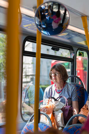 Street Photography: Elderly Lady with Glasses Sitting on City Bus in London. Редакционное