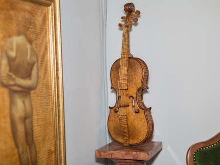 Wooden Violin resting on a Marble Column next to a Classic Painting.
