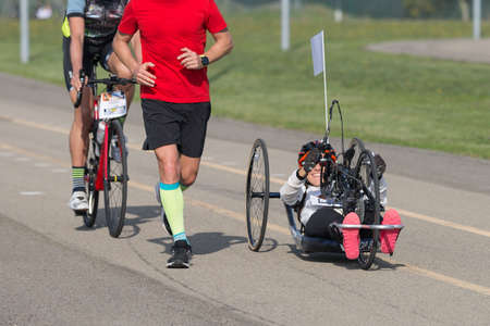 Disabled Athlete who Trains with her Hand Bike with Cyclist and Runners at her Side.