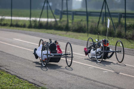 Couple of Disabled Athlete training with Their Hand Bikes on a Track. Banco de Imagens