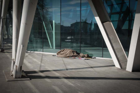 Homeless Sleeping under Warm Blankets over a Modern design Bridge.