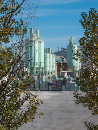 Outdoor Space of a Glass Factory with Vertical Tanks and selected Glass Materials Stacked together.