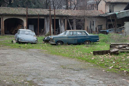 Old Worn and Rusty Cars abandoned in a Field and Crumbling Warehouse in the background.