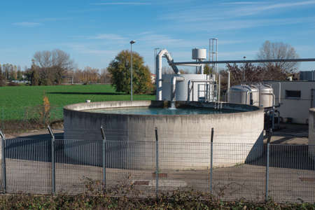 Large Circular Open-air Industrial Tank with Running Water Tap.