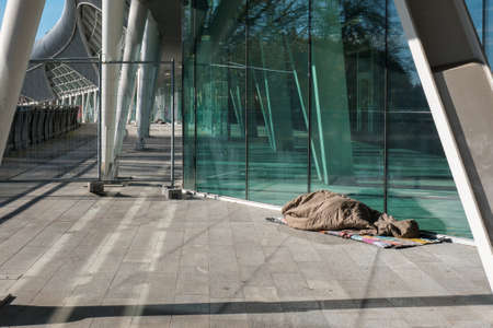 Homeless Sleeping under Warm Blankets over a Modern design Bridge.