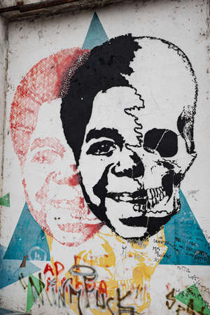 Painting on a Wall in a City depicting Actor Gary Coleman on Half a Face a Skull on the other Half.