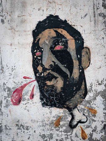 Painting on a City Wall depicting a Head of a Man with Fiery Eyes Spitting Red Liquid from his Mouth and a Bone under his Neck.
