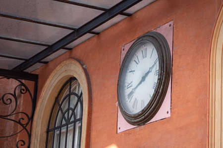Antique Clock with Roman Numerals Placed on the Wall of the Local Public Transport Bus Headquarters, Parma - Italy. 免版税图像