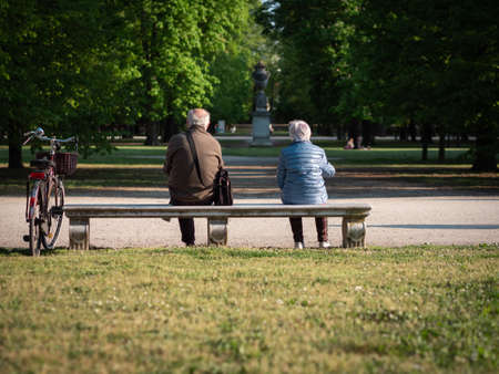 An Elderly Man and Woman Sitting far Apart on a Bench in a Public Park.