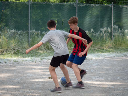 Two Teenage Boys Playing Soccer on a Dusty Field.