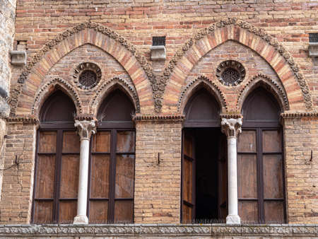 Detail of Two Windows in a Building with Exposed Bricks in the Medieval Tuscan Town of San Gimignano - Italy. Фото со стока