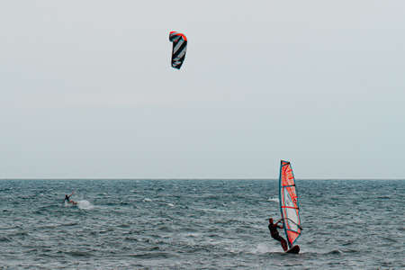 Kitesurfing and Windsurfing During a Windy Day with a Very Rough Sea. Фото со стока