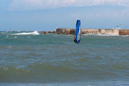 Windsurf Riding the Waves in a Choppy Sea.