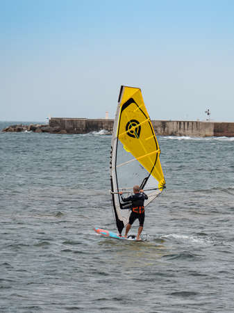 Yellow windsurf  Riding the Waves in a Choppy Sea.
