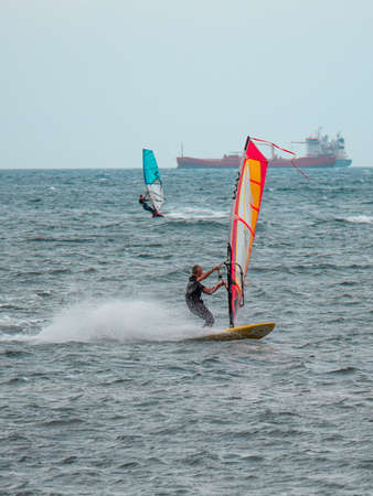 Orange and Blue windsurfing Riding the Waves in a Choppy Sea and Big Boat on Background.