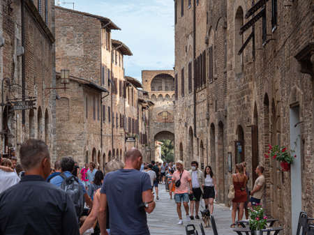 Crowds of Tourists Visit the Medieval Village of  San Gimignano, Siena - Italy. Фото со стока