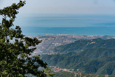 View of the marble Quarries of Carrara, the paths carved into the side of the mountain and the town of Carrara and the Coast in front of it.