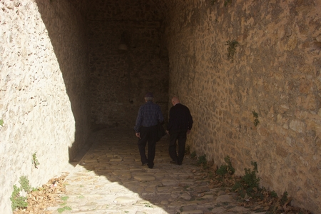 Two old men walking into the gate of an ancient castle in the darkness in Ioannina city Greece Foto de archivo