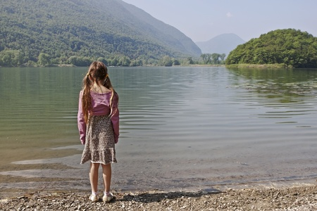 a seven years old girl is enjoying a morning at a small lake in Italy