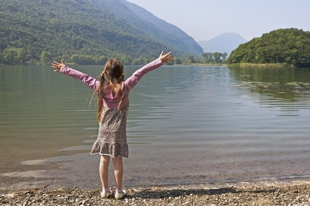 lebensfreude: a seven years old girl is enjoying a morning at a small lake in Italy