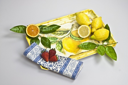 a tray with orange, lemons and strawberries
