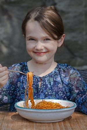 seven year old: seven year old girl is eating spaghetti outside