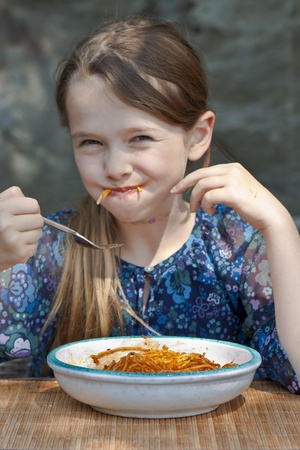 seven year old girl is eating spaghetti outside