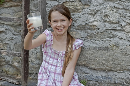 seven year old: seven year old girl is drinking milk outside in the summer