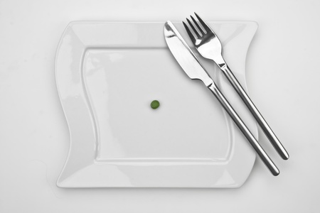 one pea on a white plate with fork and knife Stock Photo