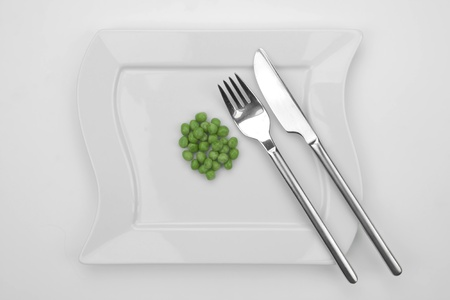 a bunch of peas on a white plate with fork and knife Stock Photo