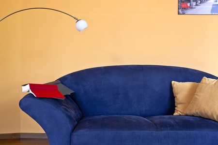 a reading corner with a blue couch, a book and a reading lamp