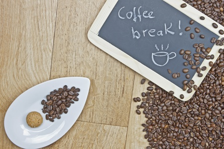 Coffee beans with cookies on a white plate and a board