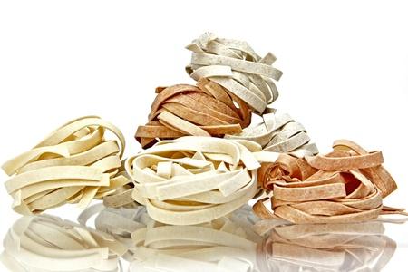 Tagliatelle pasta in three colors on white background