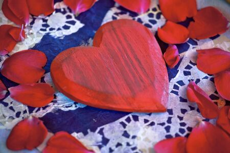a red wooden heart in the middle of rose petals
